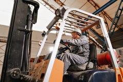 Équipez conduire un chariot élévateur par un entrepôt dans une usine conducteur dans l'uniforme et le casque de protection Le con photos libres de droits
