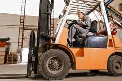 Équipez conduire un chariot élévateur par un entrepôt dans une usine conducteur dans l'uniforme et le casque de protection Le con images libres de droits