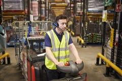 Équipez conduire un tracteur de remorquage par un entrepôt de distribution photo libre de droits