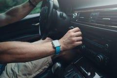 Équipez conduire une voiture et accorder la radio, montre intelligente sur la main, à l'intérieur photos libres de droits