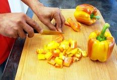 Équipez couper les poivrons rayés sur un hachoir en bois Photos libres de droits