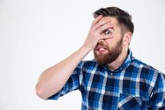 Équipez couvrir son visage de paume et regarder l'appareil-photo par des doigts photographie stock