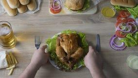 Équipez dépendant au poulet frit de mise de consommation malsaine sur la table, amour pour la nourriture banque de vidéos