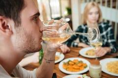 Équipez dîner et boire du vin avec des amis sur la cuisine Photo stock