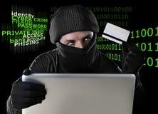 Équipez dans la carte de crédit se tenante noire utilisant l'ordinateur portable d'ordinateur pour l'activité criminelle entailla Photos libres de droits