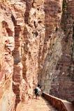 Équipez descendre des étapes de montagne près de pierre énorme Photographie stock