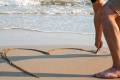 Équipez dessiner un coeur sur le sable au concept d'amour de coucher du soleil Photo stock