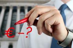 Équipez dessiner un signe d'euro avec la question par le stylo rouge photo stock