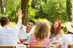 Équipez donner à de hauts cinq à l'des amis et des filles riant pendant le lu Image libre de droits