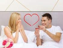Équipez donner à femme peu de boîte et anneau rouges dans lui Photos libres de droits