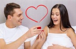 Équipez donner à femme peu de boîte et anneau rouges dans lui Photos stock