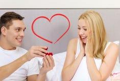 Équipez donner à femme peu de boîte et anneau rouges dans lui Image stock