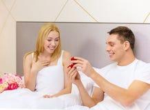 Équipez donner à femme peu de boîte et anneau rouges dans lui Photographie stock