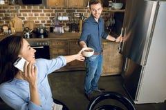 Équipez donner à la femme avec des boules de maïs de chocolat de smartphone dans la cuvette Image stock