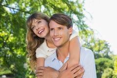 Équipez donner à sa jolie amie un ferroutage dans le sourire de parc Photo libre de droits