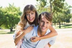 Équipez donner à sa jolie amie un ferroutage en parc souriant à l'appareil-photo Photo libre de droits
