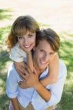 Équipez donner à sa jolie amie un ferroutage en parc souriant à l'appareil-photo Image libre de droits