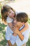 Équipez donner à sa jolie amie un ferroutage en parc souriant à l'un l'autre Photo libre de droits