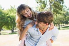 Équipez donner à sa jolie amie un ferroutage en parc souriant à l'un l'autre Photographie stock