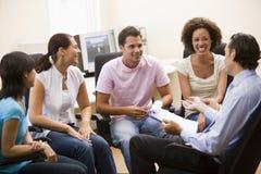 Équipez donner la conférence à quatre personnes dans la salle des ordinateurs Image stock