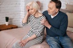Équipez donner la consolation à son épouse supérieure avec le mal de tête Photographie stock