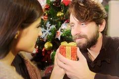 Équipez donner le cadeau de Noël à l'amie souriant dans l'amour Photo libre de droits