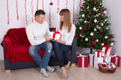 Équipez donner le cadeau de Noël à son épouse ou amie dans les décorums Image libre de droits