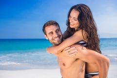 Équipez donner sur le dos à son amie à la plage Photos stock