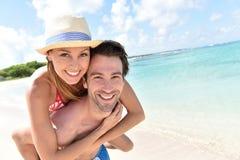 Équipez effectuer son amie de retour sur la plage des Caraïbes Photo stock