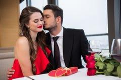 équipez embrasser l'amie de sourire pendant la date romantique dans le restaurant, St Photographie stock libre de droits