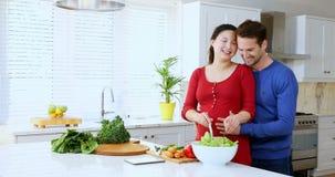 Équipez embrasser la femme enceinte tout en préparant la salade au comptoir de cuisine 4k banque de vidéos