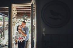 Équipez embrasser la femme par derrière tout en préparant le smoot de pastèque photo stock