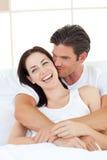 Équipez embrasser sa amie riante dans la chambre à coucher Images libres de droits