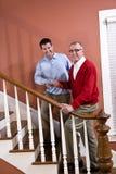 Équipez en aidant le père aîné pour monter des escaliers à la maison Photographie stock libre de droits