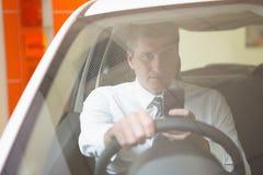 Équipez envoyer un texte se reposant dans sa voiture photo libre de droits