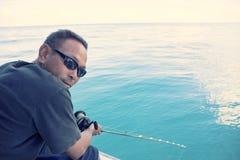 Équipez et canne à pêche à disposition avec la scène bleue large de mer Images libres de droits