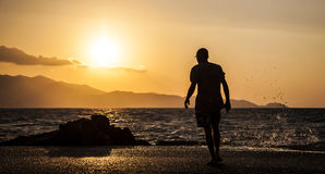 Équipez et des vagues éclaboussant sur un beau coucher du soleil Photographie stock libre de droits