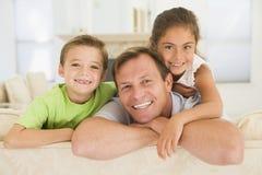 Équipez et deux enfants en bas âge s'asseyant dans la salle de séjour Images libres de droits