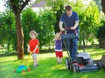 Équipez et deux petits garçons d'enfant de mêmes parents ayant l'amusement avec la tondeuse à gazon Photo libre de droits