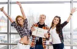 Équipez et la femme deux tenant un passeport avec des billets et une carte et regardez l'appareil-photo heureux Recueilli dans un Image libre de droits