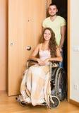 Équipez et son épouse dans le fauteuil roulant à la porte Photo stock