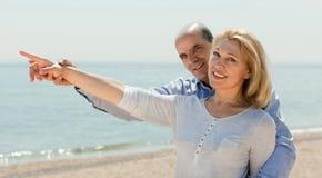 Équipez et son épouse montrant quelque chose dans la distance au bord de la mer Photographie stock libre de droits