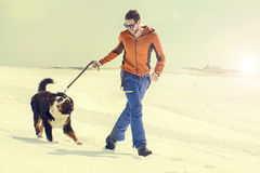 Équipez et son chien fonctionnant dans la neige au coucher du soleil en montagne Photo libre de droits
