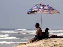 Équipez et son crabot détendant à la plage Photographie stock libre de droits