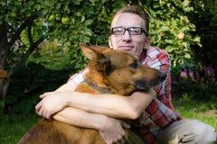 Équipez et son repos de chien dans le jardin Image libre de droits