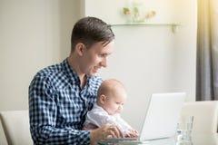 Équipez et un bébé travaillant à l'ordinateur portable photo stock