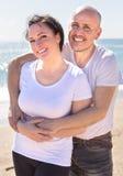Équipez et une femme d'une cinquantaine d'années dans le T-shirt blanc caressant sur le bea Images libres de droits