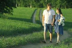 Équipez et une femme enceinte à la nature d'été Image stock