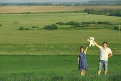 Équipez et une femme enceinte dans le domaine d'été Photographie stock