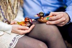 Équipez et une femme tenant des paires de canards en bois, concept de la famille Image stock